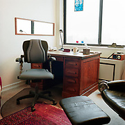 A black office type chair in front of a wooden desk, a large sliding glass window in the background, a mirror on the wall, a black chair and footrest on the right, and the reflection of the city and a flexible table lamp in the mirror.