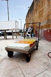 Quando il pesce arriva in porto, viene scaricato e trasportato grazie a questi carrelli. Quest'ultimo fotografato davanti ad una pescheria di Brindisi, fà quasi da cornice al pescivendolo che si riposa seduto.