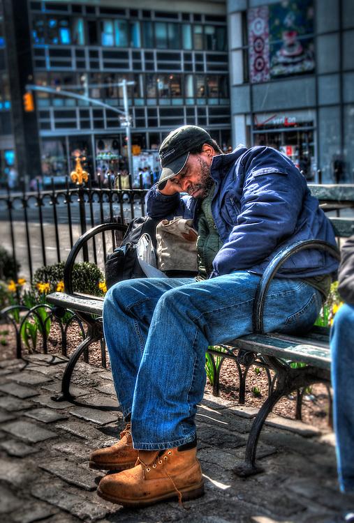 Man sleeping on Manhattan park bench