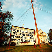 During a journey into America's hinterlands, days after the September 11th attacks in New York and Washington DC, a sign spelling out a message of faith and patriotism is seen outside the Upper Seneca Baptist church in Cedar Grove, Maryland. The preacher has written God Bless America but has misspelled 'devastation' that the Devil is bringing. Messages and slogans appeared all over America following the trauma and the desire for retribution following the terrorist attacks that killed thousands, Christians wanted reprisals as emotions ran high in the media. Small community churches preached against Islam in the same breath as the Devil's evil. The rhetoric of the Crusades as said by President Bush was also a popular way of stirring the propaganda for invasion and war. .