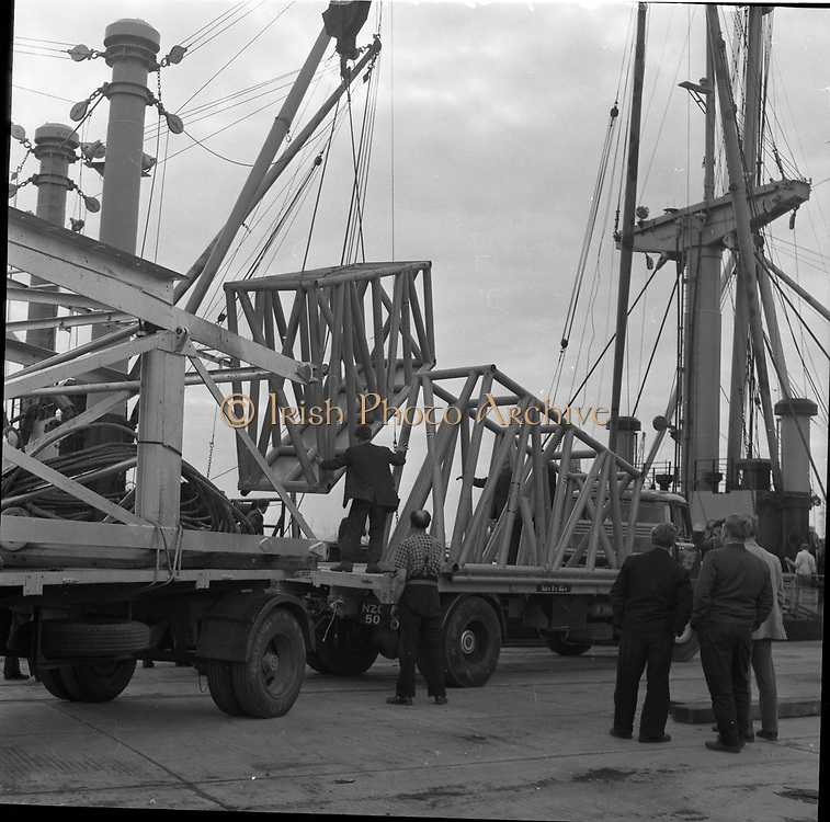 """31 July 1962<br /> Oil drilling equipment arrives at North Wall, Dublin. Image shows unloading of oil drilling machinery for Ambassador Irish oil. The equipment is being loaded onto CIE trucks including a Leyland from the ship """"Kendall""""."""