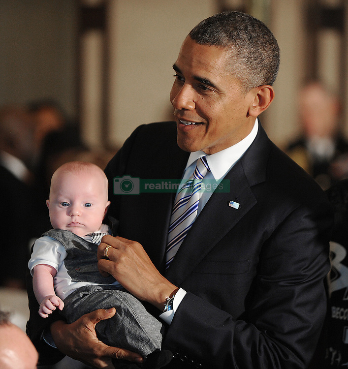 President Barack Obama holds a baby at a Father's Day luncheon to celebrate the importance of strong families and mentorship in the State Dining Room of the White House in Washington, DC, USA, June 14 , 2013.Fathers and their children as well as students and leaders from the Becoming a Man (BAM) program at Hyde Park Academy in Chicago attend the event. Photo by Olivier Douliery/ABACAPRESS.COM  | 368992_006 Washington Etats-Unis United States