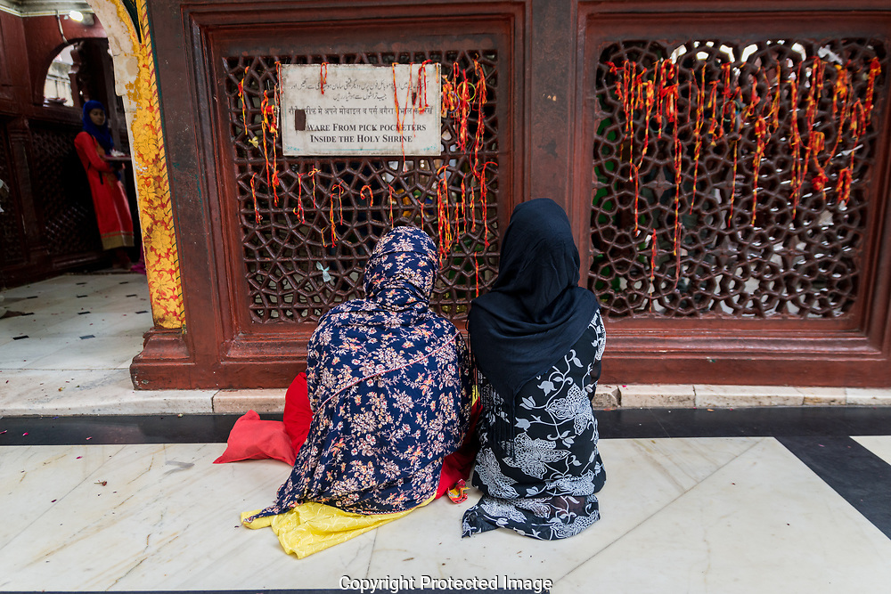Women pray for male heirs, tying threads to the jali screen asking the Shaykh for assistance.
