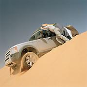 Men rock 4x4 to help vehicle over crest of dune in the Sahara Desert, Libya