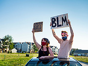 17 JUNE 2020 - NORWALK, IOWA: Residents of Norwalk, IA, stand up in their car to watch a Black Lives Matter march go through the community. About 400 supporters of Black Lives Matter marched through Norwalk, IA, an upper class suburb of Des Moines Wednesday. Norwalk has a population of about 10,000 and, according to the US Census Bureau, is 97 percent white. The marchers were protesting police violence against people of color. The march was a reaction to the police killing of George Floyd in Minneapolis in May. The march was peaceful.        PHOTO BY JACK KURTZ