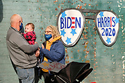 """16 OCTOBER 2020 - PERRY, IOWA: A couple with a child waits for a """"Get Out the Vote"""" event with Doug Emhoff, the husband of Vice Presidential Candidate Kamala Harris. Emhoff spoke to a group of about 30 people. The crowd was socially distanced and masks were required in  keeping with CDC and state of Iowa health guidelines to deal with the COVID-19 pandemic. Emhoff is traveling throughout Nebraska and Iowa today, campaigning on behalf of the Biden/Harris ticket.        PHOTO BY JACK KURTZ"""