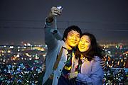 Junges Paar fotografiert sich in abendlicher Stimmung auf der unteren Aussichtsplattform des N Seoul Towers in der koreanischen Haupstadt umringt mit Wünschen versehenen Schlössern. Der N Seoul Tower ist ein der Öffentlichkeit zugänglicher Fernsehturm in der südkoreanischen Hauptstadt Seoul. Der 236,7 Meter hohe Turm steht auf 243 m ü. N.N. des Berges Namsan.<br /> <br /> Young couple photographing each other during an evening mood at the lowest observation deck of the N Seoul Tower surrounded by lockers. N Seoul Tower is a communication tower located in Seoul, South Korea. Built in 1969, and opened to the public in 1980, the tower measures 236.7 m (777 ft) in height (from the base) and tops out at 479.7 m (1,574 ft) above sea level.