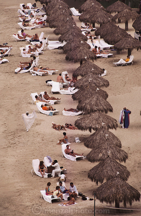 The beach at the Camino Real Hotel with tourists sunbathing by thatched cabanas in Puerto Vallarta, Mexico.