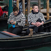 VENICE, ITALY - FEBRUARY 16:  RTwo Gondoliers take a break during the passage of the traditional regatta which officially opens the Venice Carnival  on February 16, 2014 in Venice, Italy. The 2014 Carnival of Venice will run from February 15 to March 4 and includes a program of gala dinners, parades, dances, masked balls and music events.  (Photo by Marco Secchi/Getty Images)