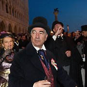 """VENICE, ITALY - FEBRUARY 19:  Members of the association """"Amici del Carnevale di Venezia"""" wearing 19th century costumes enjoy live music in St Mark Square on February 19, 2011 in Venice, Italy. The fountain pouring wine features today during the Gran brindisi a Venezia or Grand Toast in Venice, the opening ceremony of this year Carnival ."""
