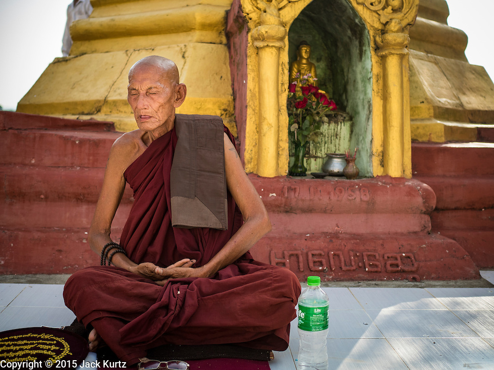 28 OCTOBER 2015 - THANLYNN, MYANMAR:  A monk in meditation during observances of Thadingyut at Kyaik Khauk Pagoda. The Thadingyut Festival, the Lighting Festival of Myanmar, is held on the full moon day of the Burmese Lunar month of Thadingyut. As a custom, it is held at the end of the Buddhist lent (Vassa). The Thadingyut festival is the celebration to welcome the Buddha's descent from heaven.     PHOTO BY JACK KURTZ