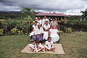 The Lagavale family, dressed in their Sunday best for the White Sunday holiday church services, cheerfully pose for the camera in Poutasi Village, Western Samoa. The Lagavale family lives in a 720-square-foot tin-roofed open-air house with a detached cookhouse in Poutasi Village, Western Samoa. The Lagavales have pigs, chickens, a few calves, fruit trees and a vegetable garden. They farm, fish, and make crafts to support themselves. They also work for others locally, which supplements their modest needs. Material World Project.