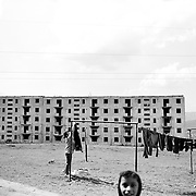 A lady hangs out the washing as children play in a housing estate surrounded by unfinished communist style housing blocks which still stand in the heart of the housing estate of the small Romanian town of  Copsa Mica, Transylvania, Romania. Copsa Mica was once described as the most polluted town in Europe. May 9, 2008. Photo Tim Clayton....Copsa Mica, a small industrial town deep in Transylvania, Romania, was described during the 1990s as the most polluted town in Europe with lead levels reaching were more than 1000 times the allowable International limits and life expectancy nine years shorter than the National average...The pollution was caused entirely by two factories, Carbosin produced black for dies and tires and closed in 1993 while Sometra, a nonferrous smelter is still operational today...The pollution was so bad sheep were black, covered in soot and health officials advised against eating livestock or vegetables and drinking the water or milk...The Communist rule of Nicolae Ceausescu is blamed for the widespread environmental degradation that left industrial parts of Romania in ecological disaster. Industry was situated in a way to concentrate pollution in small areas leaving the rest of the country relatively free of pollution.Copsa Mica in particular was left an environmental disaster...The pollution caused a direct affect on human health with widespread Lung disease, Impotency, the highest infant mortality rate in Europe, Lead poisoning andbehavioral problems...Fifteen years on since the closure of Carbosin in 1993, the factory skeleton remains as part of the towns bleak landscape, Unfinished communist style housing blocks still stand in the heart of the towns housing estate. The town's inhabitants arestill trying to recover from the long lasting effects of pollution...Recent survey's found the soil contained so much lead that it was 92 times above the permitted level; the vegetation had a lead content 22 times above the permitted l