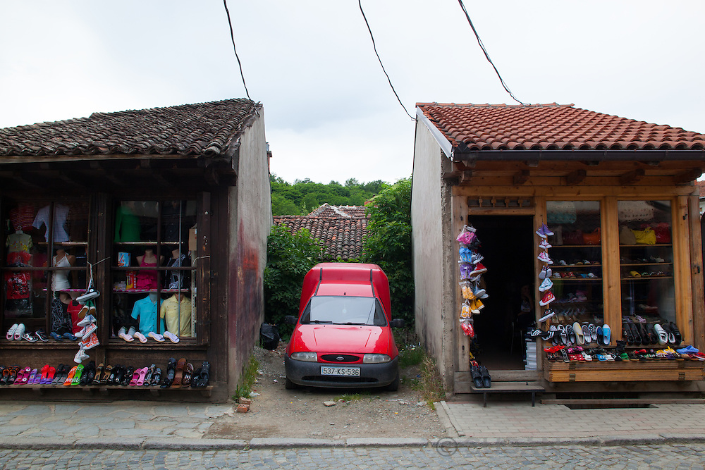 Car parked between two small buildings in Djakova, Kosovo.