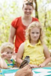 Man holding bird getting banded, with children in background, Mitchell Lake Audubon Center, San Antonio, Texas, USA.