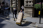 A middle-aged man carefully delivers boxes across a road junction in the City of London.