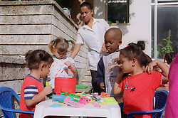Children and teacher at nursery school in Havana; Cuba; playing with plastic toys,