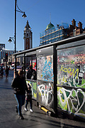 A lady leads a child past a graffiti-covered bus stop in Brixton, on 30th january 2019, in Lambeth, south London, England.