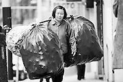 A woman walks on the streets of Chinatown in San Francisco carrying large bags full of cans.