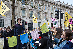 London, UK. 9th March, 2019. A boy addresses climate activists from Extinction Rebellion after they poured artificial blood on the ground outside Downing Street as part of an act of civil disobedience named 'The Blood of Our Children' to call on the Government to take immediate steps to combat the current climate and ecological emergency.