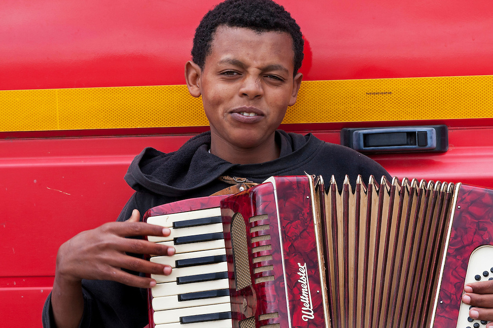Young boy playing an accordion,The Jungle, refugee camp, France