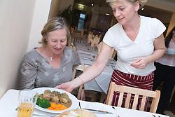 Waitress putting plate of Golabki on table at Polish restaurant,