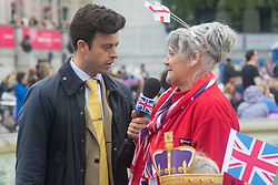Trafalgar Square, London, June 12th 2016. Rain greets Londoners and visitors to the capital's Trafalgar Square as the Mayor hosts a Patron's Lunch in celebration of The Queen's 90th birthday. PICTURED: Satirical broadcaster Jolyon Rubinstein interviews a woman.