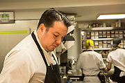 New York, NY, - December 8, 2013. Chef Matt Lambert in the kitchen. Behind him two cooks work near a rack of clear bins containing spices and herbs.