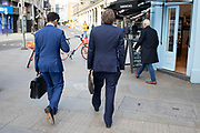 Two businessmen in different shades of blue suits walking through Covent Garden holding attache cases on 25th February 2020 in London, United Kingdom. In recent years the blue suit has become increasingly popular among men, instead of the more traditional greys.