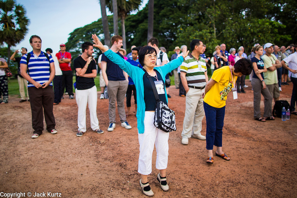 """02 JULY 2013 - ANGKOR WAT, SIEM REAP, SIEM REAP, CAMBODIA:  A tourist does tai-chi exercises while she waits for the sunrise at Angkor Wat. Angkor Wat is the largest temple complex in the world. The temple was built by the Khmer King Suryavarman II in the early 12th century in Yasodharapura (present-day Angkor), the capital of the Khmer Empire, as his state temple and eventual mausoleum. Angkor Wat was dedicated to Vishnu. It is the best-preserved temple at the site, and has remained a religious centre since its foundation– first Hindu, then Buddhist. The temple is at the top of the high classical style of Khmer architecture. It is a symbol of Cambodia, appearing on the national flag, and it is the country's prime attraction for visitors. The temple is admired for the architecture, the extensive bas-reliefs, and for the numerous devatas adorning its walls. The modern name, Angkor Wat, means """"Temple City"""" or """"City of Temples"""" in Khmer; Angkor, meaning """"city"""" or """"capital city"""", is a vernacular form of the word nokor, which comes from the Sanskrit word nagara. Wat is the Khmer word for """"temple grounds"""", derived from the Pali word """"vatta."""" Prior to this time the temple was known as Preah Pisnulok, after the posthumous title of its founder. It is also the name of complex of temples, which includes Bayon and Preah Khan, in the vicinity. It is by far the most visited tourist attraction in Cambodia. More than half of all tourists to Cambodia visit Angkor.         PHOTO BY JACK KURTZ"""