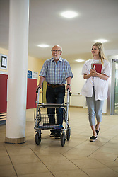Doctor and senior man with mobility walker walking down the hallway in rest home, Bavaria, Germany, Europe