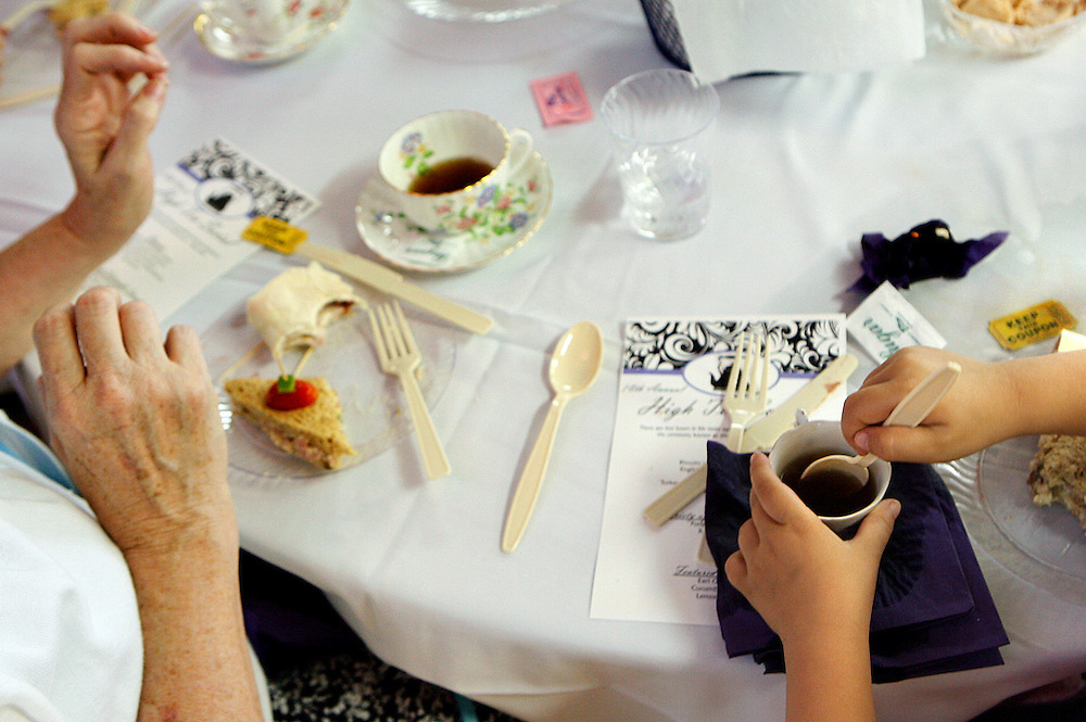 Marcy London, left, of Wenatchee, watches as her granddaughter Skylynn London, 3, stirs her tea during the 18th annual High Tea Social at the Kennewick Senior Center on May 26.