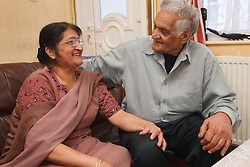 Elderly south Asian couple sharing a joke.