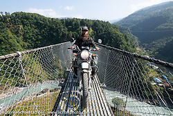 Lowbrow's Mikey Arnold, better known as Mikey Revolt, on the Kushma - Gyadi suspension bridge over the Modi River (the highest, at 384 feet, and longest, at 1,128 feet, suspension bridge in Nepal) in Motorcycle Sherpa's Ride to the Heavens motorcycle adventure in the Himalayas of Nepal. On the sixth day of riding, we went from Tatopani to Pokhara. Saturday, November 9, 2019. Photography ©2019 Michael Lichter.