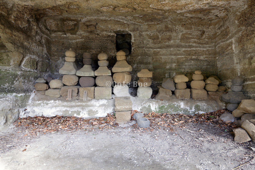 old traditional Gorinto funeral monuments inside a mountain cave in the Kamakura prefecture