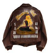 """This is a type A-2 flight jacket that was worn by a member of the 571st squadron. On the front of the jacket is the insignia for the 571st squadron, a wolf dressed in uniform gripping a bomb. The artwork on the back says """"Heavenly Cent"""" and includes a lady in black clothing sitting on her knees. Each bomb that is painted on the back signifies a completed mission."""