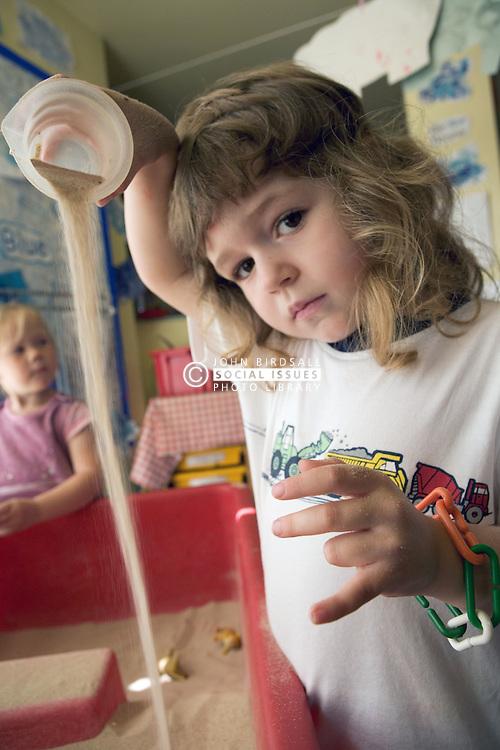Nursery School girls playing in the sandpit,