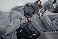At a transit camp near Molyvos, Lesvos island, Greece, migrants and refugees rest wrapped in blankets provided by the UNHCR