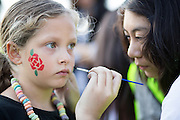 Janel Vallejo, 17, paints Savanna Archuleta's face, 6, during the 6th Annual District 4 National Night Out Resource Fair and Movie Night at Northwood Park in San Jose, California, on August 6, 2013. (Stan Olszewski/SOSKIphoto)
