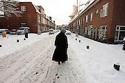 Een vrouw loopt door de besneeuwde straten in Utrecht