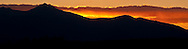 The sun slips below a silhouetted mountain lighting the sky and clouds with warm alpenglow light in northeastern Nevada, USA.