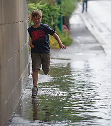 © Licensed to London News Pictures. 23/08/2013<br /> <br /> Saltburn, Cleveland, England, UK<br /> <br /> A young boy makes a dash across a flooded pavement during thunder storms that brought flash flooding under a bridge on the A174 road in Saltburn, Cleveland.<br /> <br /> Photo credit : Ian Forsyth/LNP