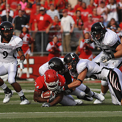 Sep 7, 2009; Piscataway, NJ, USA; Rutgers wide receiver Mason Robinson (24) is tackled by Cincinnati linebacker Andre Revels (50) and linebacker Marcus Waugh (35) during the first half of Rutgers game against Cincinnati in NCAA college football at Rutgers Stadium.