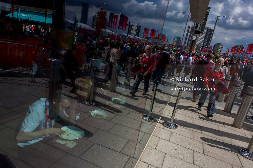 Seen through the window of a Westfield shopping mall window, an Olympic employee cleans his plate during the London 2012 Olympics, the 30th Olympiad. With the crowds of arriving spectators reflected in the background, we see the banners of the London games on a brilliant sunny day in Stratford, East London. Situated on the fringe of the 2012 Olympic park, Westfield is Europe's largest urban shopping centre providing the main access to the Olympic park with a central 'street' giving 75% of Olympic visitors access to the main stadium so retail space..