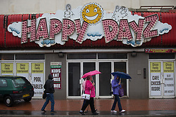 © Licensed to London News Pictures . 17/06/2015. Blackpool  , UK . Pedestrians with umbrellas raised outside the Happy Dayz amusement arcade in Blackpool . Rain and fog over Blackpool today ( Wednesday 17th June 2015 ) . Photo credit : Joel Goodman/LNP