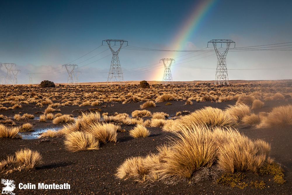 Rainbow over power plyons, Rangipo desert near Mt Ruapehu, Tongariro National Park.