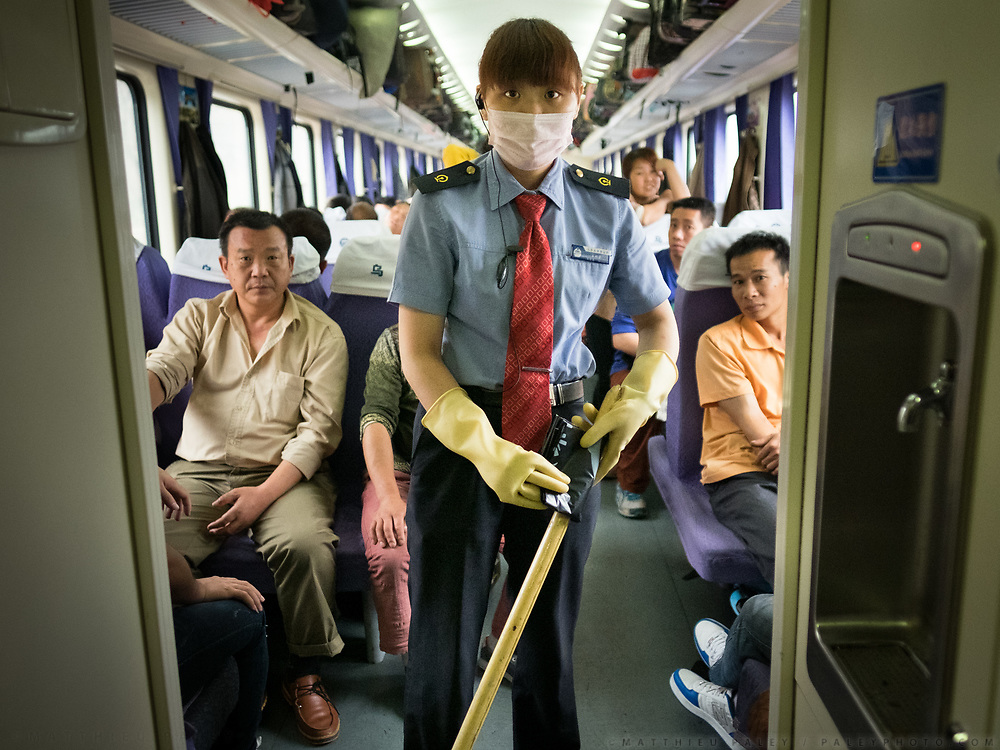 A controler staff is cleaning the floor of one of the wagon. Passengers often dispose of their garbages on the floor - so it needs to be clean every so often. Life in the seating wagons in the train from Hong Kong to Urumqi, Xinjiang.