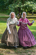 Old Bethpage, New York, USA. August 30, 2015. L-R, identical twin sisters JULIETTE FOX of Hicksville, and PATRICIA JOSEPH of College Point, wearing Civil War era style long hoop skirt clothing, are member of the Old Bethpage Village Dancers which danced throughout the Old Time Music Weekend at Old Bethpage Village Restoration, where popular music of the American Civil War period was performed, and visitors learned traditional 1800's contradances.