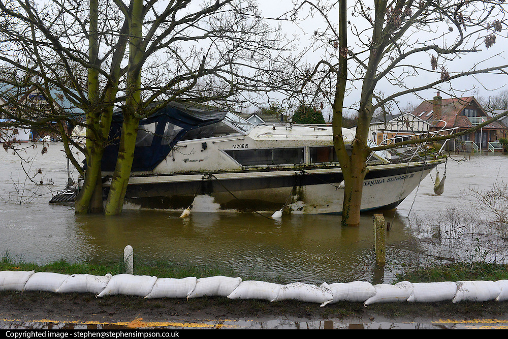 © Licensed to London News Pictures. 11/02/2014. Laleham, UK. Boats along the Thames are becoming loose from their moorings. Boat owners have been told not to try and secure them as it is dangerous. Here one lies near to sandbags lain down by the military last night.  Flooding in LALEHAM in Surrey today 11th February 2014 after the River Thames burst its banks. The Environment Agency has issued 14 Severe Flood Warnings alone the Thames. Photo credit : Stephen Simpson/LNP