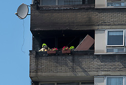 © Licensed to London News Pictures. 23/08/2019. London, UK. A fire fighter assess damage at the scene where a fire has started at a flat in a tower block at Darfield Way in west London, just yards from Grenfell Tower. Photo credit: Ben Cawthra/LNP